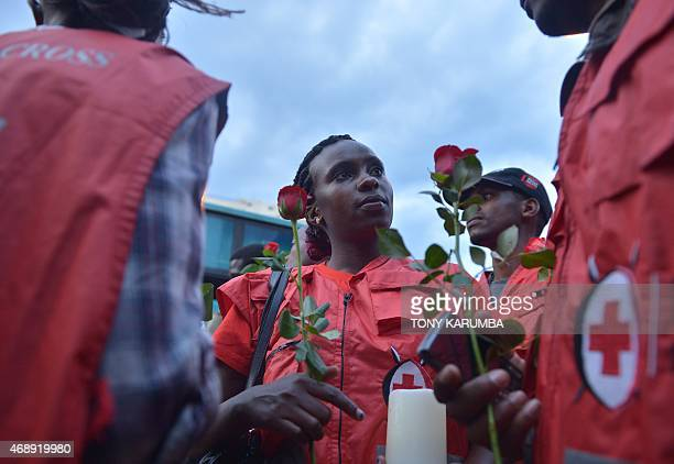 Members of the Kenyan Red Cross hold roses as they head to a monument of wooden crosses symbolically assembled in Nairobi on April 8, 2015 on the...