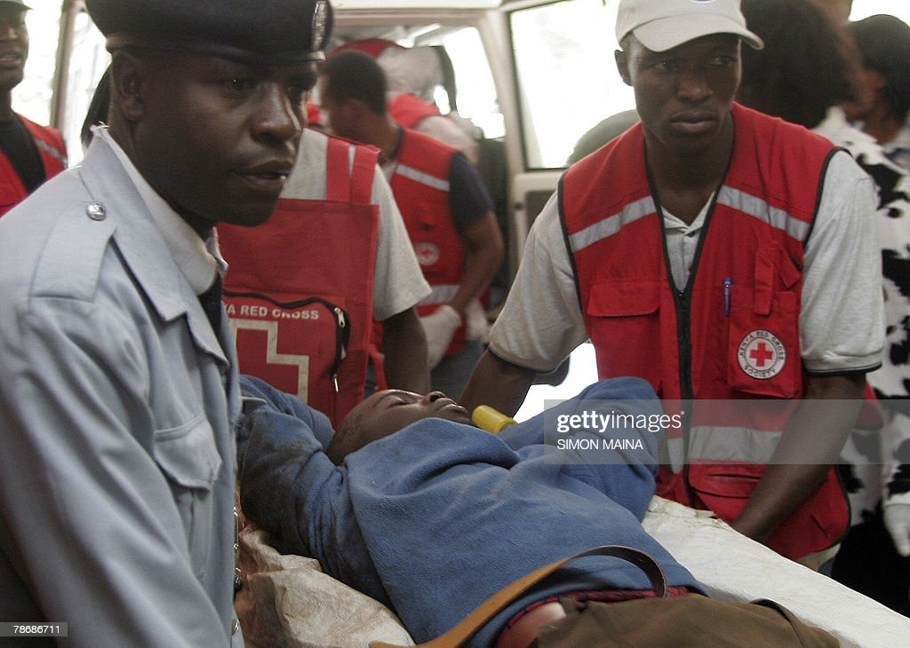 Members of the Kenyan Red Cross wheel a injured supporter of