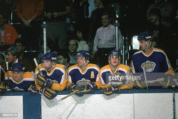 Members of the LA Kings professional hockey team watch the onice action from the bench December 1986 Visible players include coach Pat Quinn Jimmy...