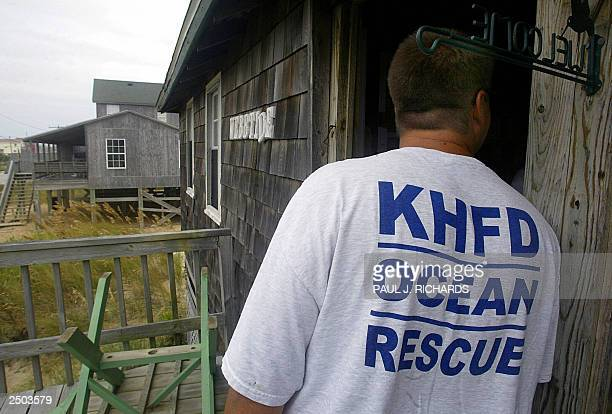 Members of the Kitty Hawk Ocean Rescue team warn a resident of a beach front home of the mandatory evacuation 17 September 2003 in the Kitty Hawk...