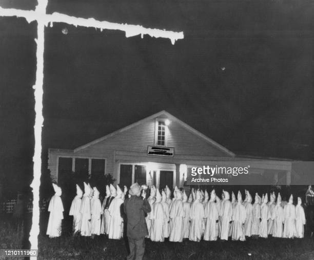 Members of the Ku Klux Klan burn a wooden cross in front of a house they wish to intimidate, US, 1954.