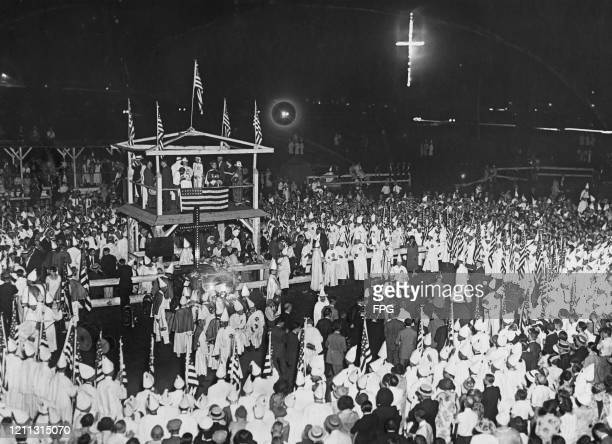 Members of the Ku Klux Klan inducting new members beneath an 80-foot burning cross in Arlington, Virginia, USA, 9th August 1925.