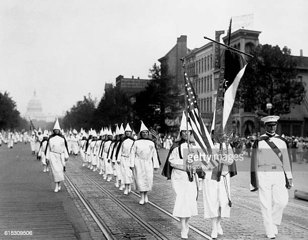 Members of the Ku Klux Klan parade down Pennsylvania Avenue Washington DC The Capitol is in background 1928