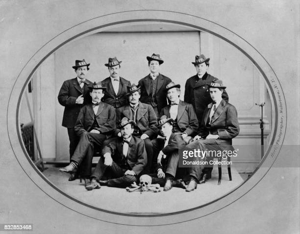"""Members of the Ku Klux Klan Watertown Division pose for a portrait wearing hats with """"KKK"""" in large letters and with a skull and bones arranged on..."""