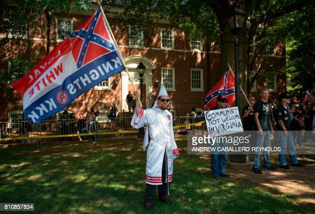 Members of the Ku Klux Klan wave flags as they hold a rally in Charlottesville Virginia on July 8 2017 to protest the planned removal of a statue of...