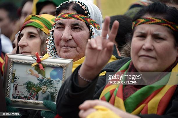 Members of the Kurdish community flash the v for victory sign in front of flags and banners of convicted Kurdistan Worker's Party leader Abdullah...