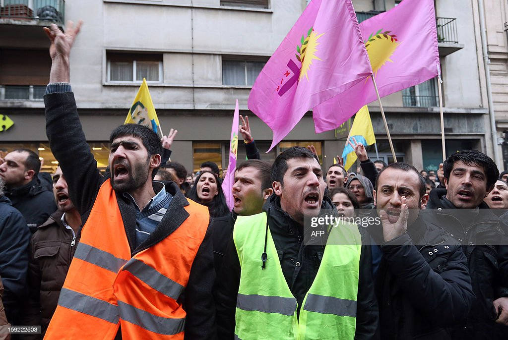 Members of the Kurdish community in France, holding portraits of yellow flags with a portrait of jailed Kurdish rebel leader Abdullah Ocalan and pink flags of the Koma Jinen Bilind (KJB, Gathering of Revolutionary Women, part of the PKK) protest on January 10, 2013, near the Kurdistan Information Bureau in Paris where three Kurdish women were found killed with a gunshot to the head. The bodies of the women were found shortly before 2:00 am (0100 GMT) inside the building in the 10th arrondissement of the French capital. One of the women was 32-year-old Fidan Dogan who worked in the institute's information centre, according to its director, Leon Edart. The identities of the other two women, who were reportedly Kurdish activists but did not work at the Institute, were not immediately available.