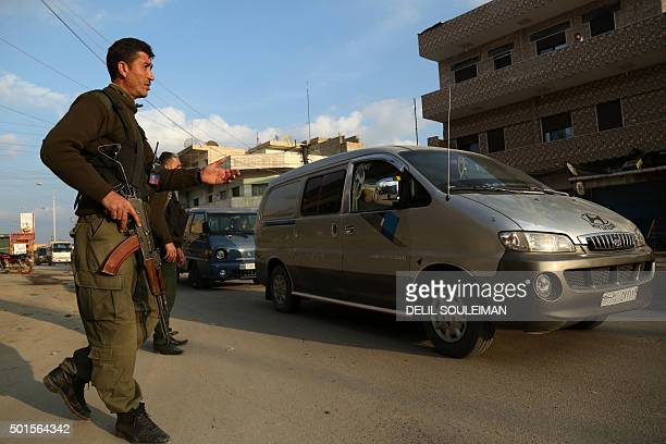 Members of the Kurdish internal security forces check vehicles on December 16 2015 in the northeastern Syrian city of Qamishli as tensions rose...