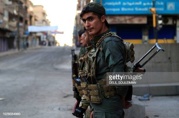 Members of the Kurdish Internal Security Police Force of Asayish keep watch during a security alert after clashes with regime forces in Qamishli...
