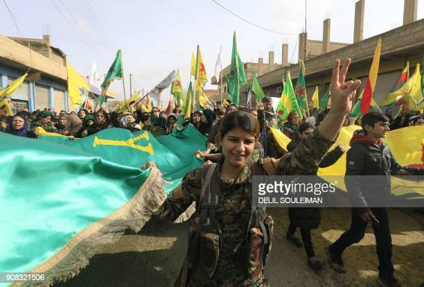 Members of the Kurdish People's Protection Units and SyrianKurds take part in a demonstration in the town of Amuda some 30 kilometres west of...