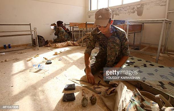 Members of the Kurdish People's Protection Units take position in a classroom in the village of Maarouf in the northeastern Syrian province of...