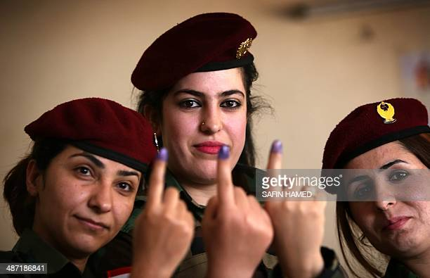 Members of the Kurdish Peshmerga force show their inkstained fingers in the northern Kurdish city of Arbil on April 28 after casting her ballot in...