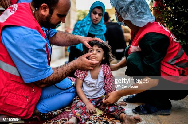 Members of the Kurdish Red Crescent check a displaced girl after she left with her father central Raqa on September 26 2017 as Syrian fighters backed...