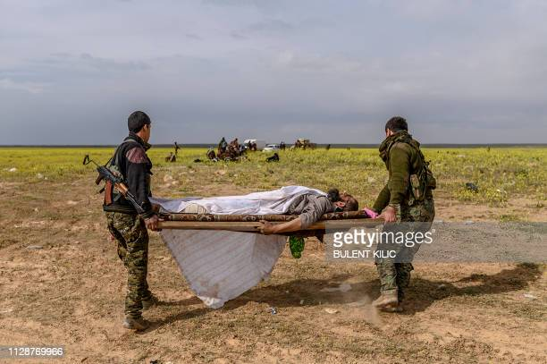 TOPSHOT Members of the Kurdishled Syrian Democratic Forces carry a man suspected of being an Islamic State group fighter after leaving the IS last...