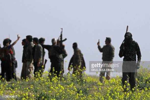 Members of the Kurdishled Syrian Democratic Forces watch a convoy of vehicles drive past carrying men identified as Islamic State group fighters who...