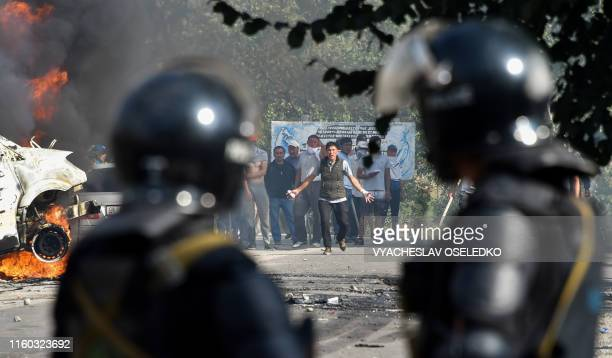 Members of the Kyrgyz special forces stand in front of protesters during clashes near Kyrgyzstan's former president residence between his supporters...