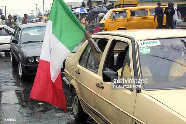 Members of the Labour Union Congress wave the union flag 21 January 2004 in a Lagos street before its leader Adams Oshiomhole announced the...