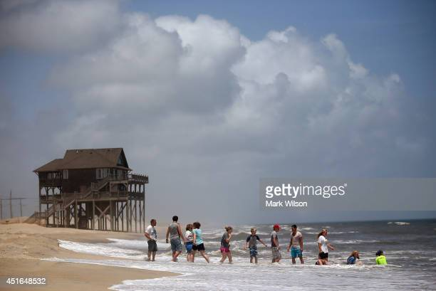 Members of the large Garrison family from Kansas City MO play in the surf before complying with the mandatory evacuation orders for Hatteras Island...
