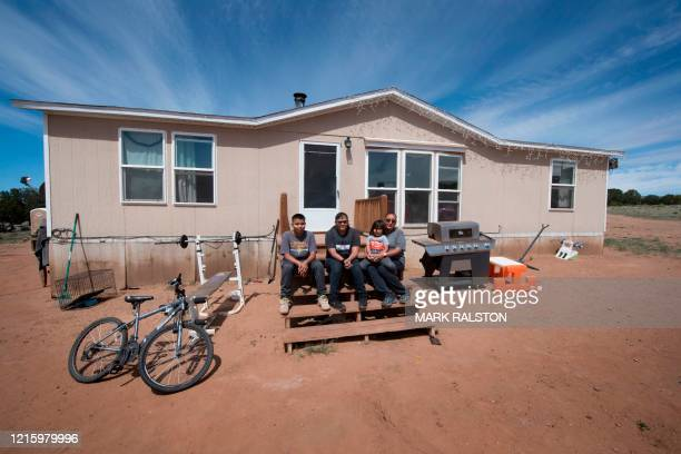 Members of the Larson family who have no running water, sit outside their home in the Navajo Nation town of Thoreau in New Mexico on May 22, 2020. -...