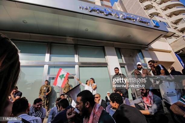 Members of the Lebanese Armed Forces stand guard as antigovernment protesters shout slogans while attempting to shut down the local branch of the...