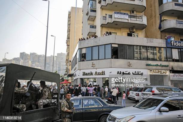 Members of the Lebanese Armed Forces stand guard as antigovernment protesters shout slogans during a demonstration in the northern port city of...