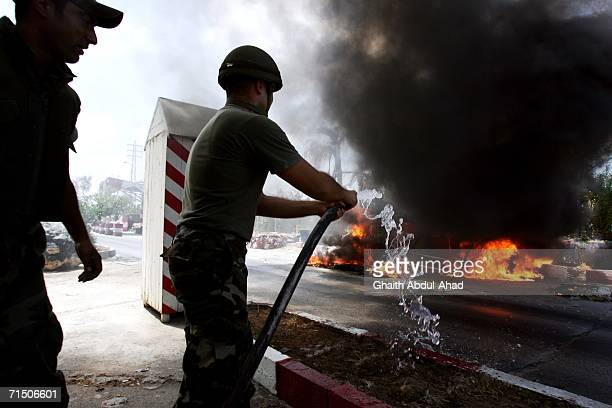 Members of the Lebanese army attempts to put out a fire in a civilian car after it was hit by an Israeli aircraft outside a hospital July 23, 2006 in...