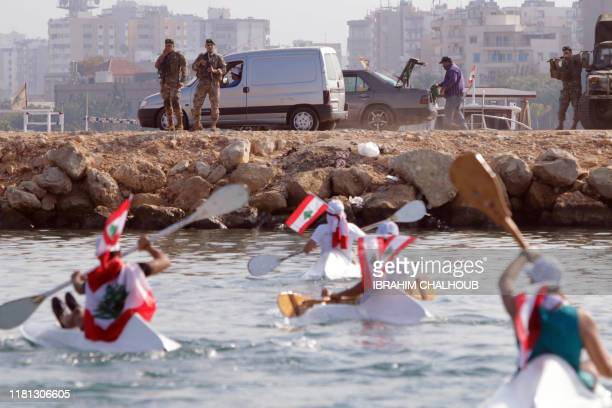 Members of the Lebanese army look from a quay at approaching antigovernment protesters on canoes as they demonstrate in the waters of the northern...