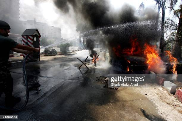 Members of the Lebanese army put out a fire in a civilian car after it was hit by an Israeli aircraft outside a hospital July 23 2006 in Tyre Lebanon...