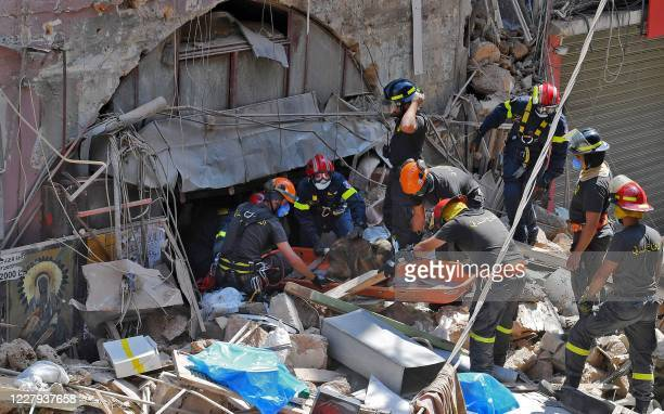 TOPSHOT Members of the Lebanese civil defence use a dog to search for victims and survivors under the rubble of a building in the Gemayzeh...