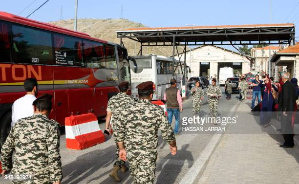 Members of the Lebanese General Security Directorate clear buses carrying Syrian refugees evacuated from the southern Lebanese village of Shebaa as...