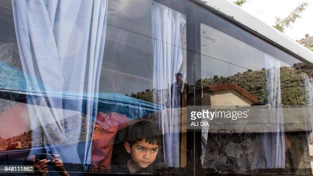 TOPSHOT Members of the Lebanese General Security Directorate stand watch as Syrian refugees ride in a bus as they are evacuated from the southern...