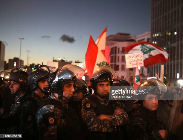 Members of the Lebanese security forces gather as antigovernment protesters rally on the eastern end of the Ring bridge that connects the western and...