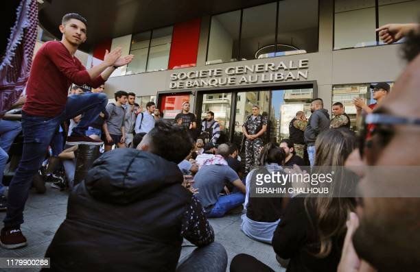 Members of the Lebanese security forces stand guard at the entrance of a bank as antigovernment protesters attempt to shut it down a during ongoing...
