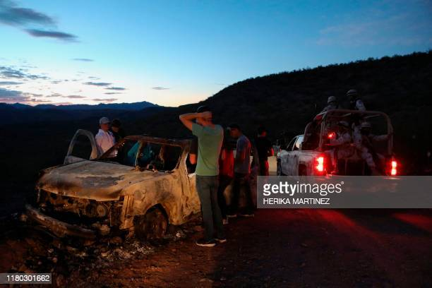 Members of the LeBaron family look at the burned car where part of the nine murdered members of the family were killed and burned during an ambush in...