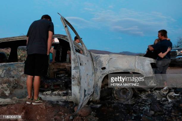 TOPSHOT Members of the Lebaron family look at the burned car where part of the nine murdered members of the family were killed and burned during an...