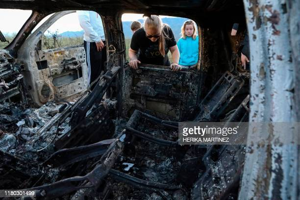 Members of the Lebaron family watch the burned car where part of the nine murdered members of the family were killed and burned during an gunmen...
