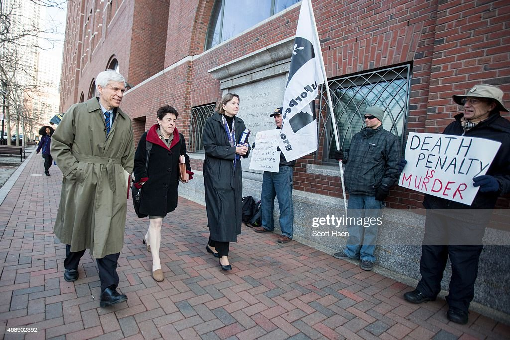 Members of the legal defense team for Boston Marathon bombing suspect Dzhokhar Tsarnaev, including David Bruck, (from left), Miriam Conrad, and Judy Clarke walk past death-penalty protesters at John Joseph Moakley United States Courthouse before deliberations begin again in the Boston Marathon Bombing case on April 8, 2015 in Boston, Massachusetts. Dzhokhar Tsarnaev, 21, has pled not guilty to 30 charges related to his involvement in the 2013 bombing, which resulted in three deaths and over 250 injuries.