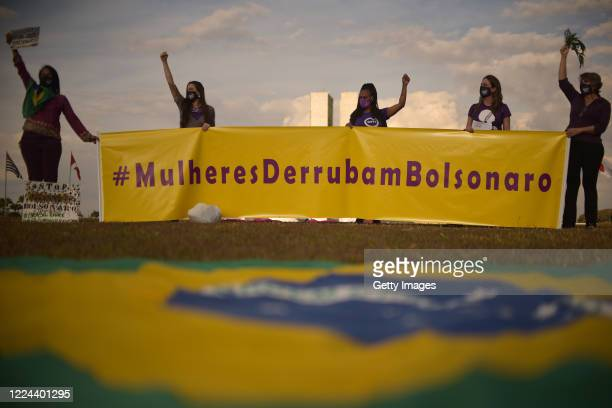 """Members of the 'Levante de Mulheres' group hold a sign that reads """"Women bring down Bolsonaro"""" during a rally against President Jair Bolsonaro in..."""