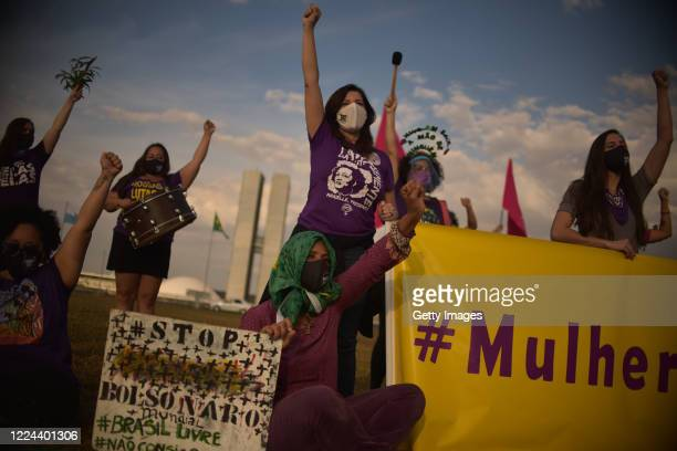 Members of the 'Levante de Mulheres' raise their fists during a rally against President Jair Bolsonaro in front of the National Congress on July 2...