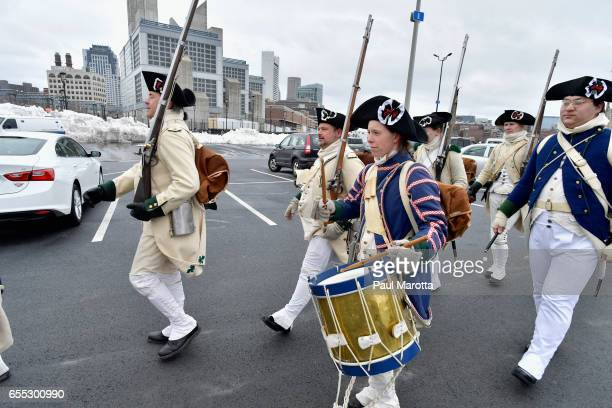 Members of the Lexington Minutemen prepare to participate in the St Patrick's Day Parade on March 19 2017 in Boston Massachusetts
