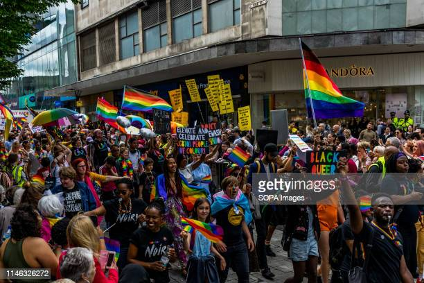Members of the LGBTQ community are seen holding rainbow flags and placards during the Birmingham Pride parade. Birmingham Pride this year is...