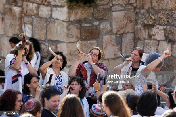 Members of the liberal Jewish religious group Women of the Wall wearing skullcaps and traditional Jewish prayer shawls known as Tallit blow Shofars...