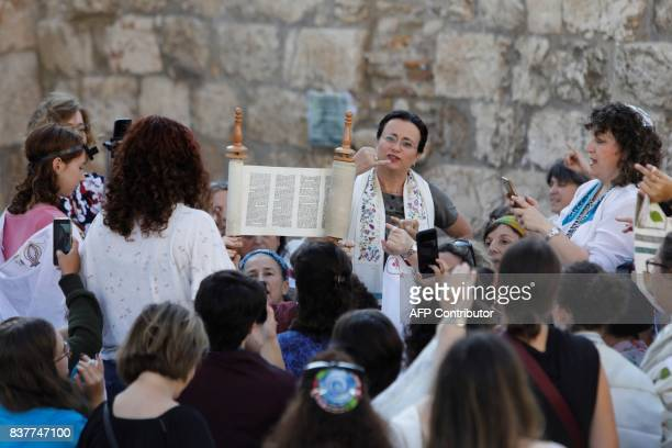 Members of the liberal Jewish religious group Women of the Wall wearing skullcaps and traditional Jewish prayer shawls known as Tallit hold up the...