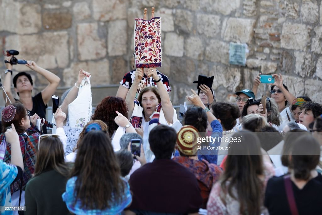 Members of the liberal Jewish religious group Women of the Wall, wearing skullcaps and traditional Jewish prayer shawls known as Tallit, hold up the Torah scroll during a morning prayer marking the first day of the Jewish month of Elul, on August 23, 2017 at the Western Wall in Jerusalem's Old City. Dozens of ultra-Orthodox men protested against the progressive activists whose movement fights for equal rights for women at the Western Wall. /