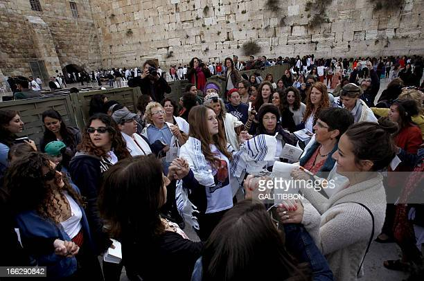 Members of the liberal religious group Women of the Wall wear phylacteries and Tallit traditional Jewish prayer shawls for men as they sing and pray...