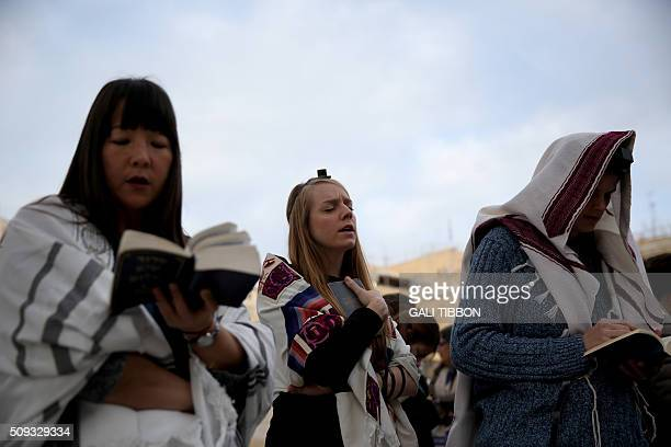 Members of the liberal religious group Women of the Wall wear phylacteries and Tallit shawls traditional Jewish prayer apparel for men as they pray...
