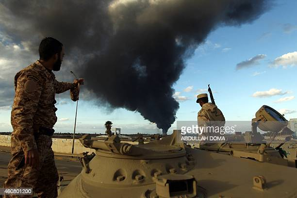 Members of the Libyan army stand on a tank as heavy black smoke rises from the city's port in the background after a fire broke out at a car tyre...