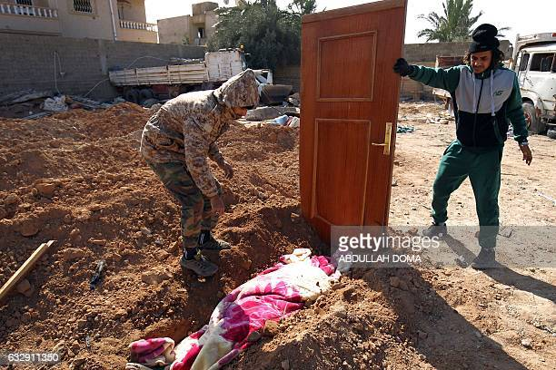 TOPSHOT Members of the Libyan National Army also known as the forces loyal to Marshal Khalifa Haftar inspect on January 28 2017 a grave of an unknown...