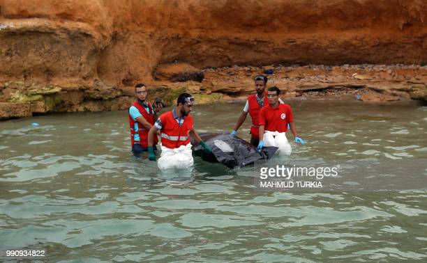 Members of the Libyan Red Crescent recover the body of a drowned migrant off the coast of Tajoura east of the capital Tripoli on July 3 2018 At least...