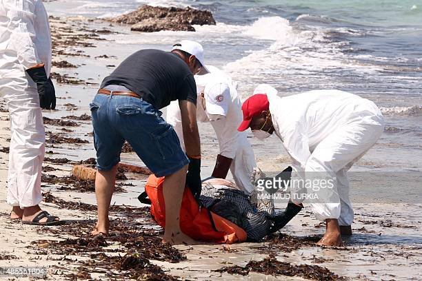 Members of the Libyan Red Crescent wearing protective white clothing and masks collect the body of a migrant that had washed ashore on a beach on...